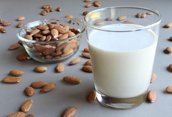 Молоко в стакане и ядра миндаля
