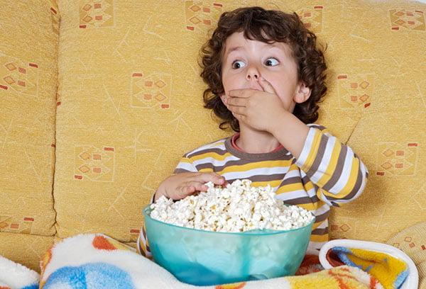 Ребенок ест попкорн