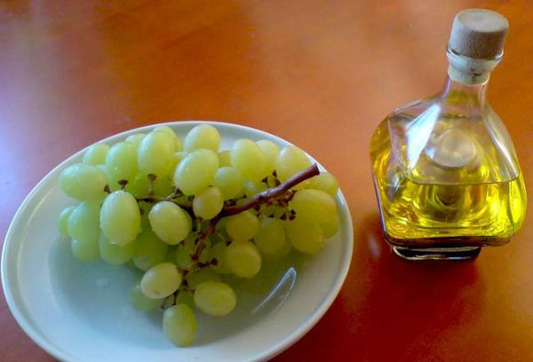белый виноград на тарелке и бутылка с уксусом