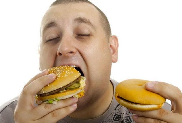 Мужчина ест гамбургеры