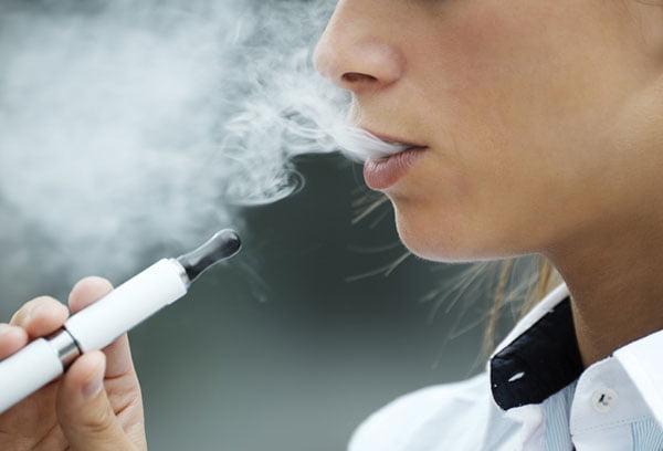 Подросток курит электронную сигарету