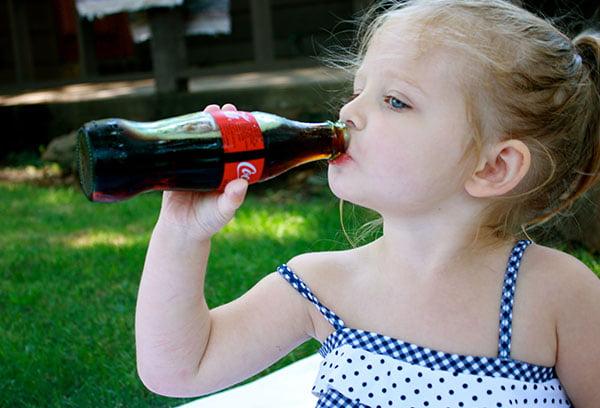 Девочка пьет кока-колу