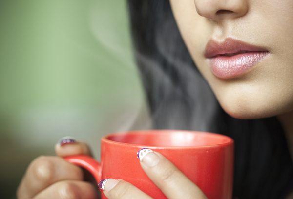 Женщина пьет горячую воду