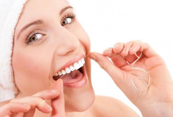 Женщина чистит зубы нитью