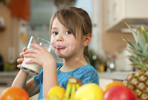 Девочка пьет кокосовое молоко