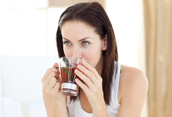 Девушка пьет отвар шиповника