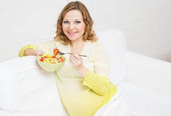 Беременная женщина ест кашу с фруктами