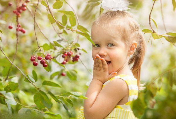 маленькая девочка у вишневого дерева