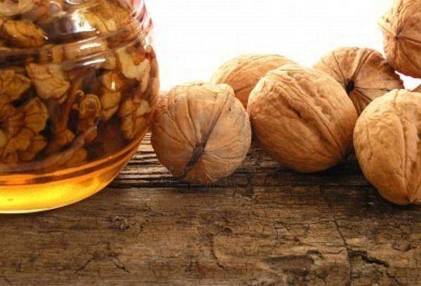 мед с орехами в стеклянной банке и грецкие орехи