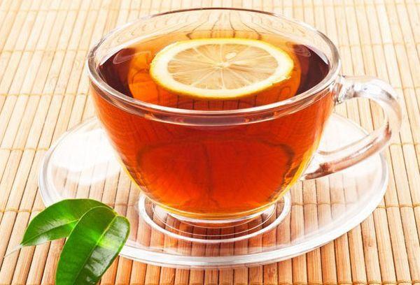 черный чай с лимоном в стеклянной чашке