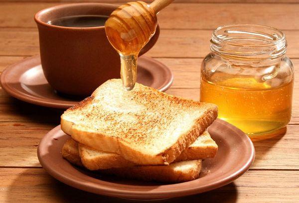 куски хлеба на тарелке и чай с медом