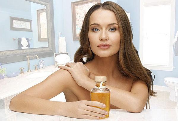 Девушка наносит на кожу масло