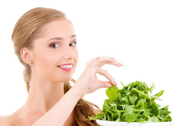 Девушка ест шпинат
