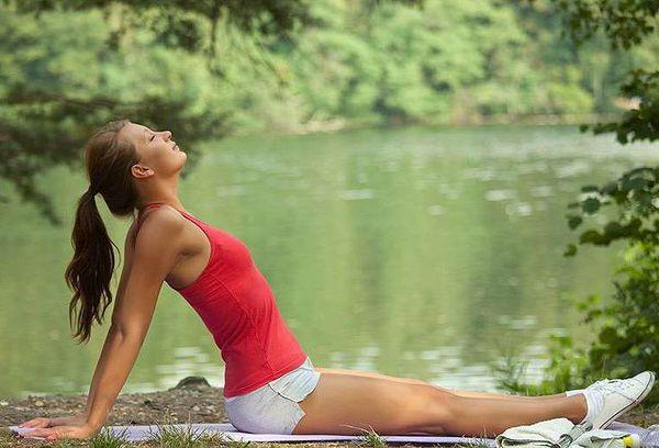 девушка на природе делает дыхательную гимнастику Стрельниковой