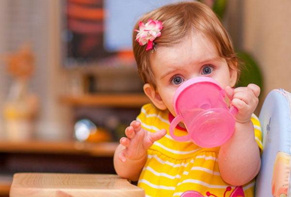 Маленькая девочка пьет сок