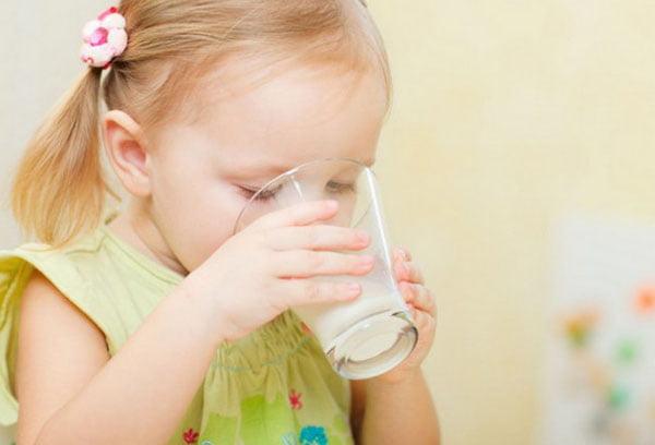 Девочка пьет молоко с медом