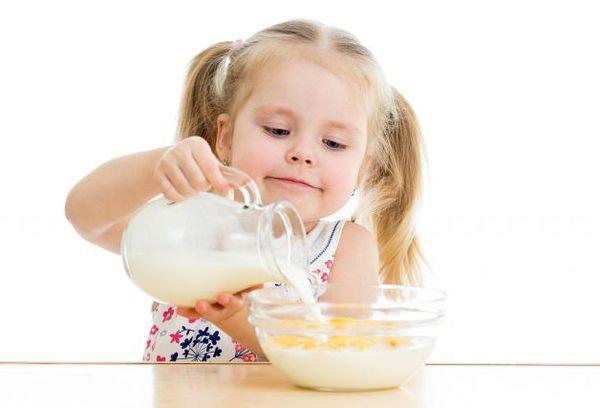 девочка заливает молоком хлопья