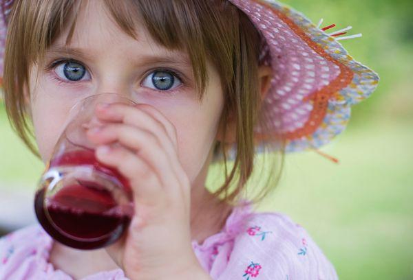 Девочка пьет виноградный сок