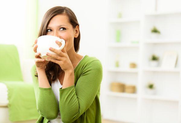 Девушка в зеленом свитере пьет чай