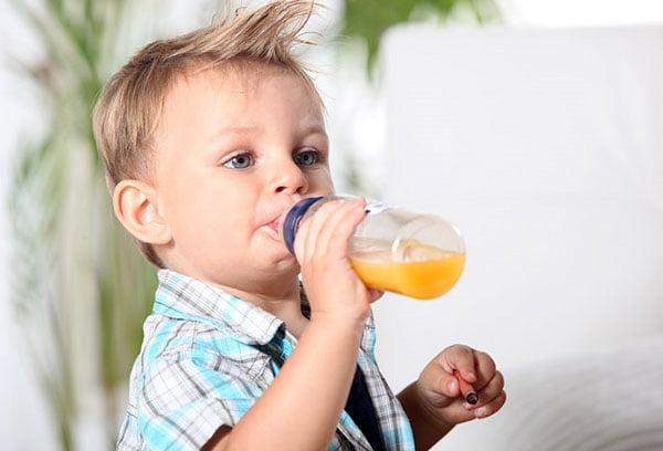 Ребенок пьет фруктовый сок