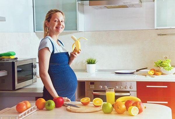 Беременная женщина ест банан