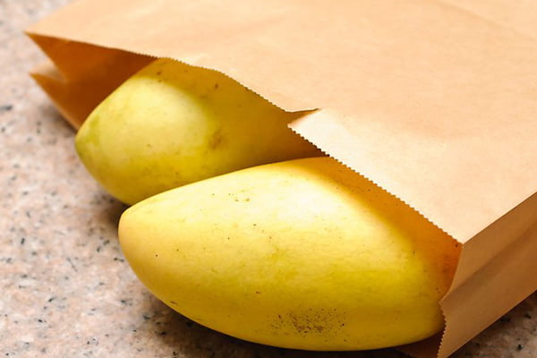 Плоды манго в бумажном пакете