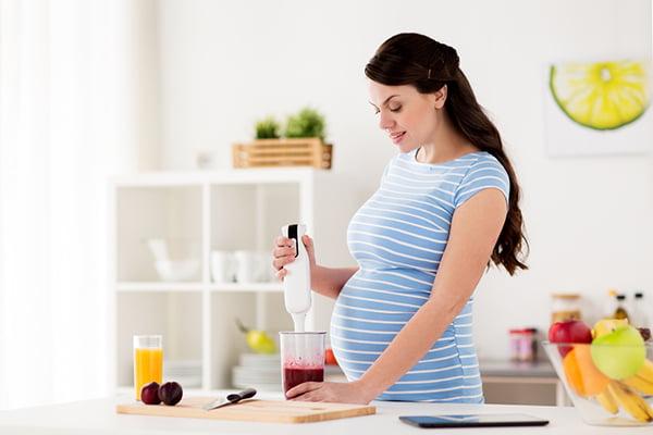 Беременная женщина готовит сливовый смузи