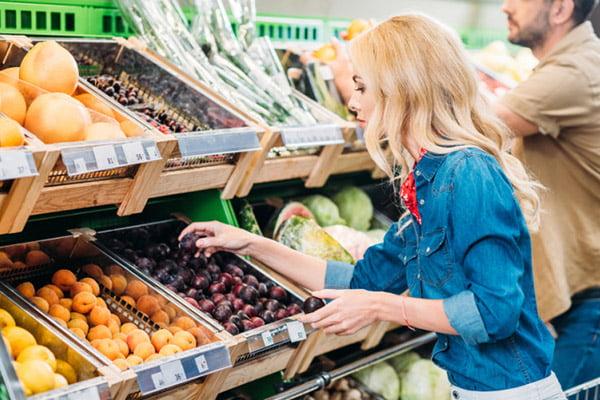 Девушка выбирает сливы в магазине