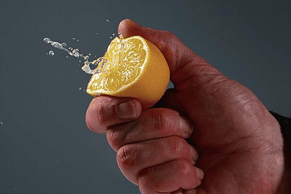 Мужчина давит половинку лимона