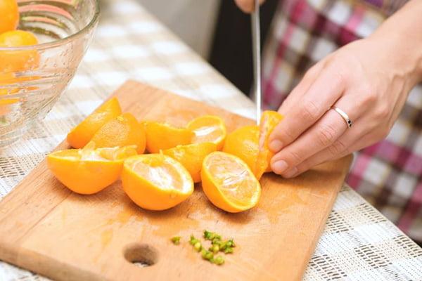 Женщина режет мандарины