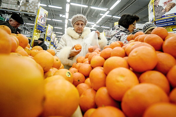 Женщина выбирает мандарины