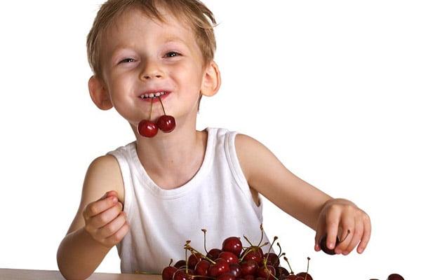 Мальчик ест черешню