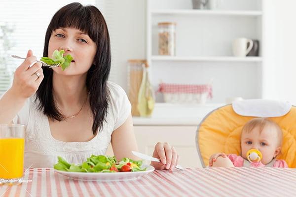 Молодая мама ест салат