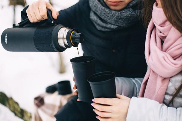 Пара пьет чай из термоса на улице