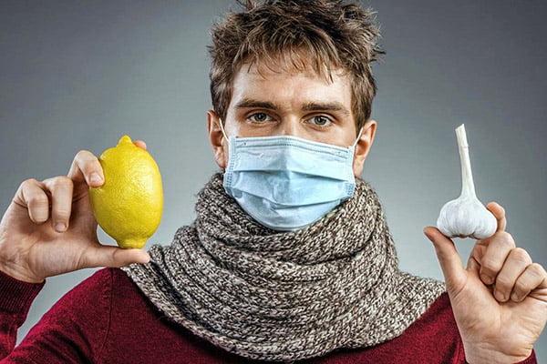 Мужчина в медицинской маске держит чеснок и лимон