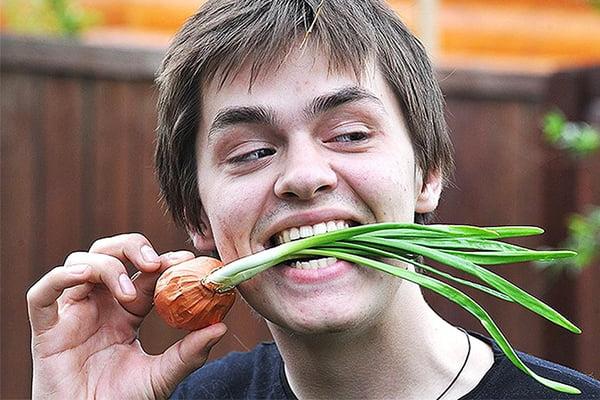 Молодой человек с луком в зубах