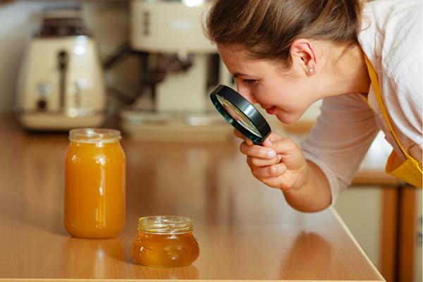 Женщина рассматривает мед под лупой