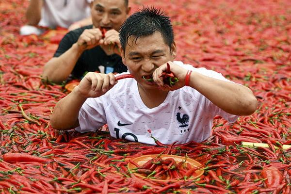 Мужчины едят жгучий перец